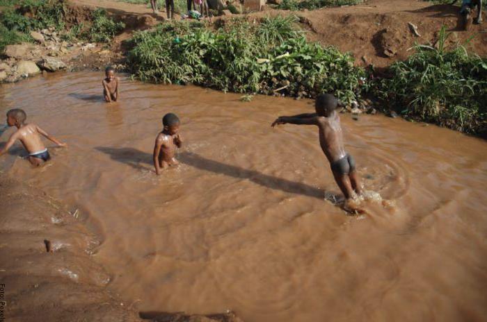 Foto de niños nadando en agua sucia