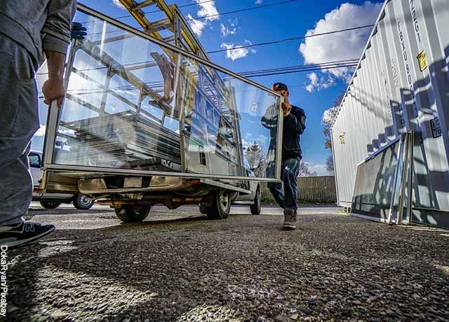 Foto de dos personas cargando vidrio que muestra lo que es soñar con trasteo