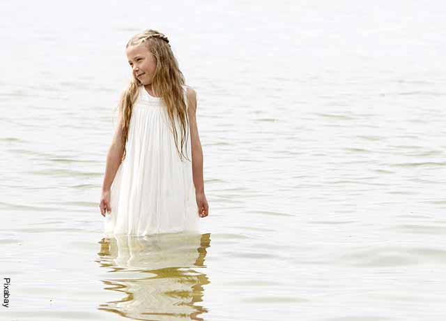 Foto de una niña con un vestido metida en el agua que revela lo que es soñar con vestido blanco
