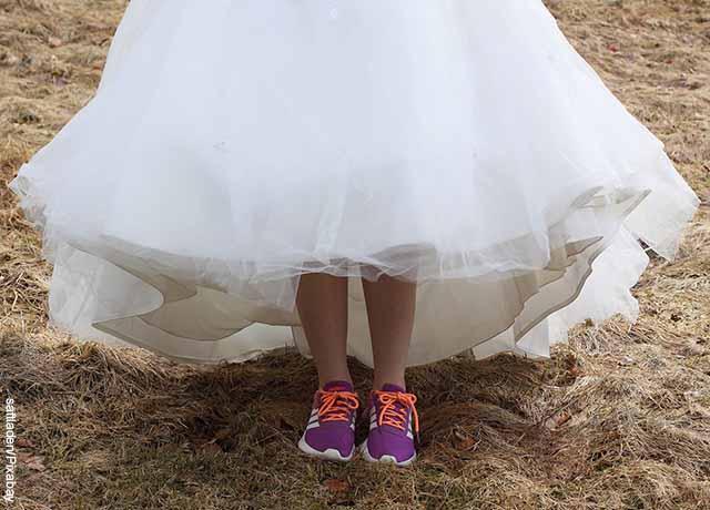 Foto de los pies de una mujer que arrastra un vestido de baño y tiene tenis de correr
