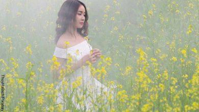 Foto de una mujer caminando entre plantas amarillas que muestra lo que es soñar con vestido blanco