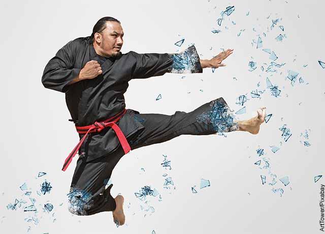 Foto de un karateca saltando rompiendo vidrios