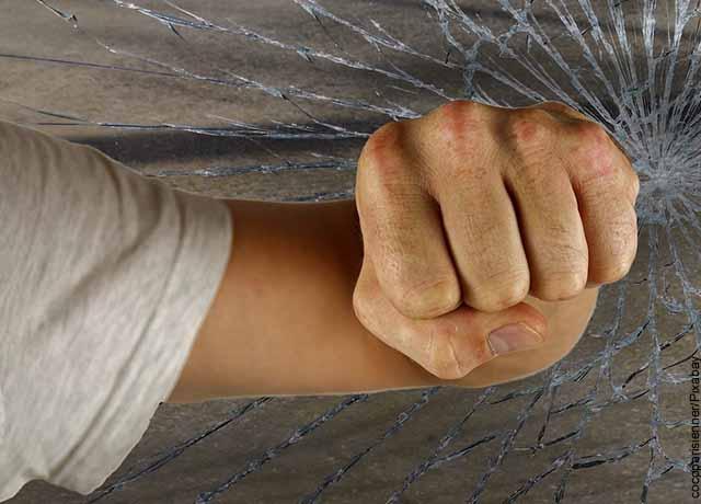 Foto de un hombre rompiendo vidrios con su puño