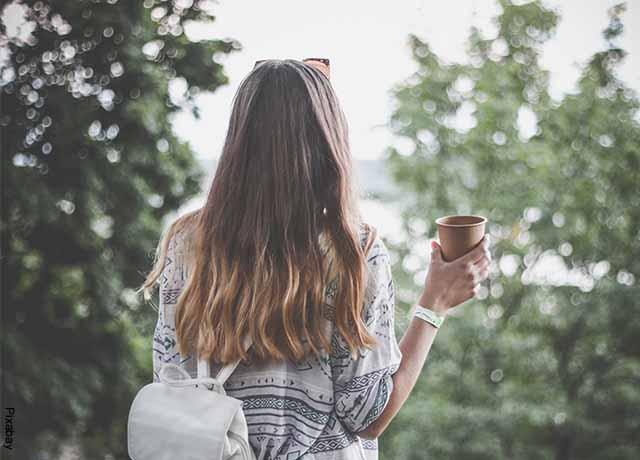 Foto de una mujer de espaldas tomando café