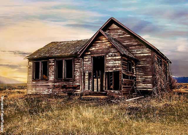 Foto de una casa de madera dañada y vacía que ilustra lo que es soñar con casa