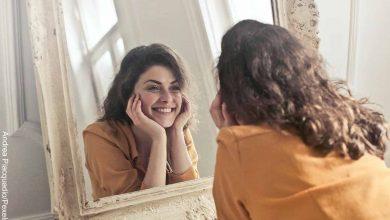 Foto de una mujer mirándose al espejo mientras sonríe que muestra el ácido salicílico para qué sirve