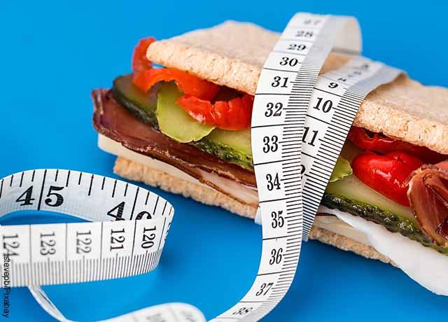 Foto de un sándwich con un metro enrollado