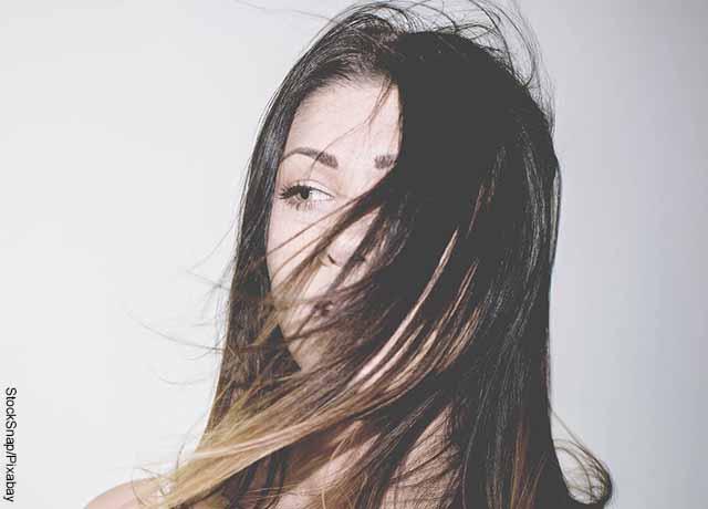 Foto del cabello de una mujer cayendo sobre su rostro