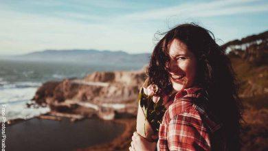 Foto de una mujer feliz y sonriendo en la playa que revela la biotina para qué sirve