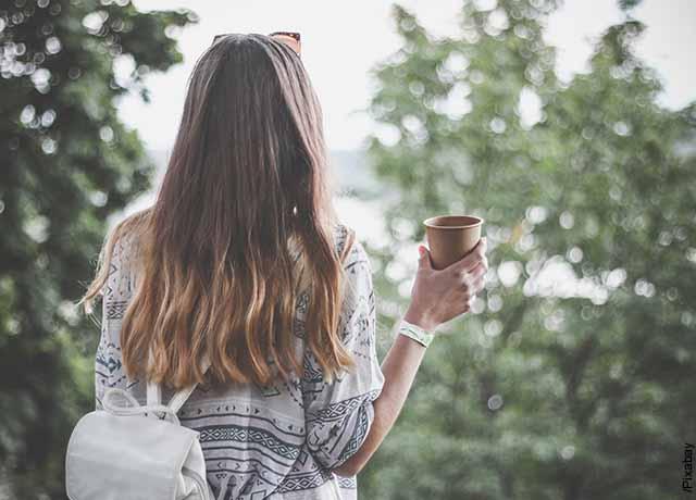Foto de una mujer de espalda sosteniendo una taza