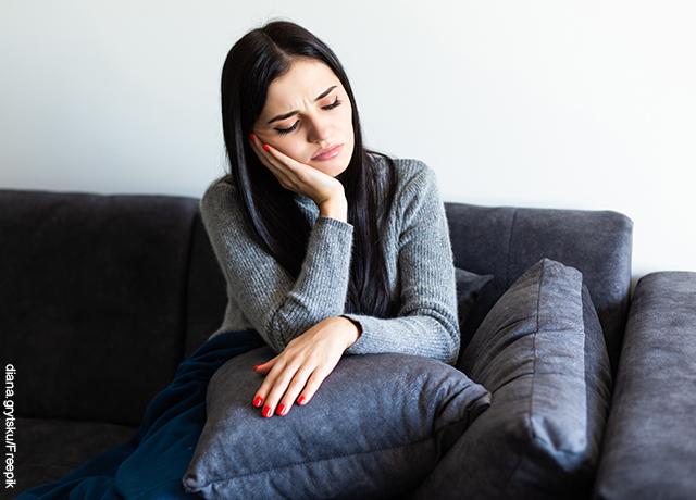 Foto de una mujer malhumorada en un sofá que muestra cuándo empiezan los síntomas del embarazo