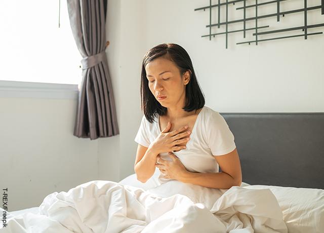 Foto de una mujer sentada en la cama tomándose el pecho