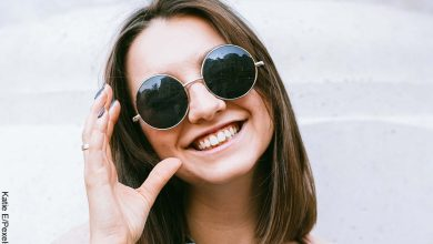 Foto de una mujer joven de pelo corto sonriendo con gafas oscuras puestas y que revela las imágenes de cortes de cabello