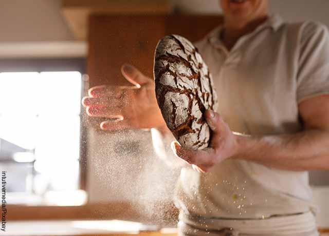 Foto de un panadero espolvoreando un pan redondo