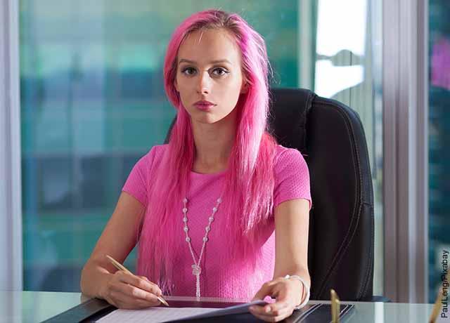 Foto de una mujer de cabello rosado sentada en un escritorio