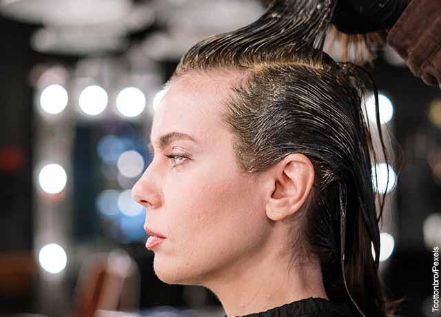 Foto de una modelo a la que le aplican un tiente en el pelo