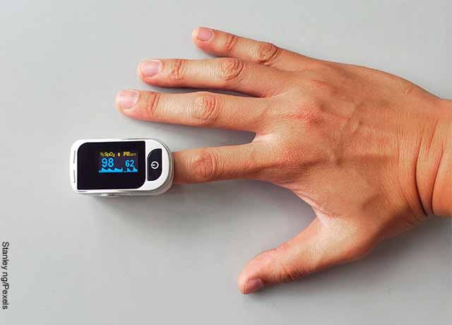 Foto de la mano de un hombre con un aparato digital médico en uno de sus dedos