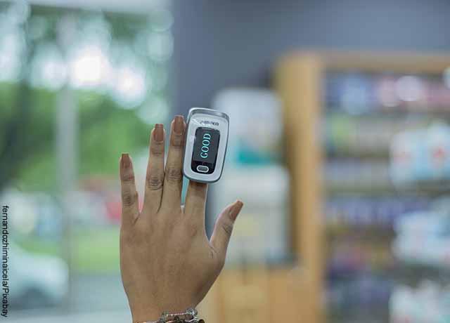 Foto de la mano de una mujer con un aparato conectado a su dedo