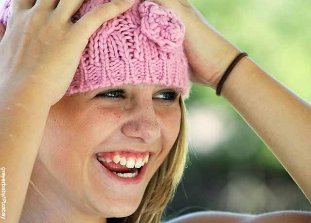 Foto de una noven sonriendo mientras toma su cabeza que muestra para qué sirve el ácido fólico
