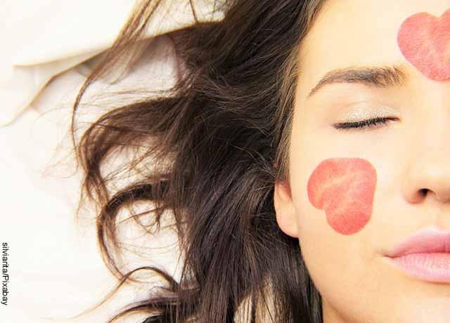 Foto del rostro de una mujer con pétalos de rosa sobre ella