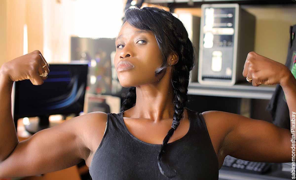 Foto de una mujer levantando sus brazos con fuerza que revela para qué sirve el ácido fólico
