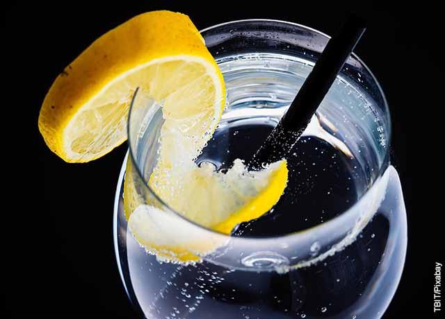 Foto de una copa de agua con pitillo y una rodaja de lima
