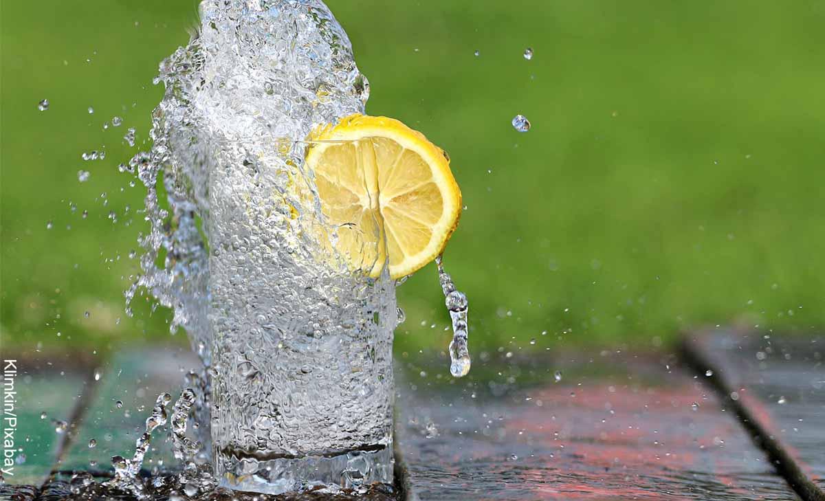 Foto de un vaso de agua regándose de un vaso que revela para qué sirve el agua tibia con limón