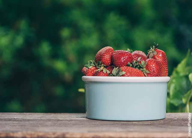 Foto de una taza de fresas en una vasija de porcelana