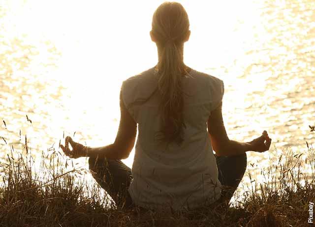 Foto de una mujer meditando frente a un lago