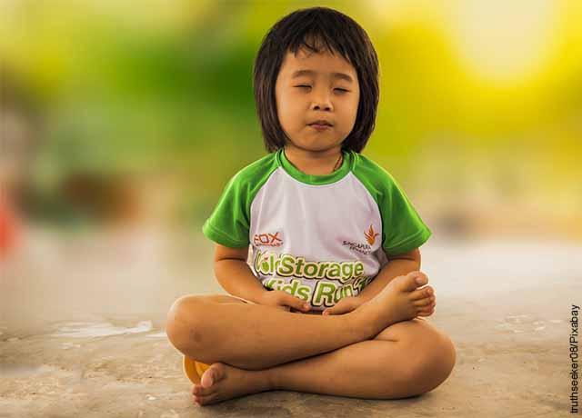 Foto de una niña asiática meditando que revela para qué sirve la meditación