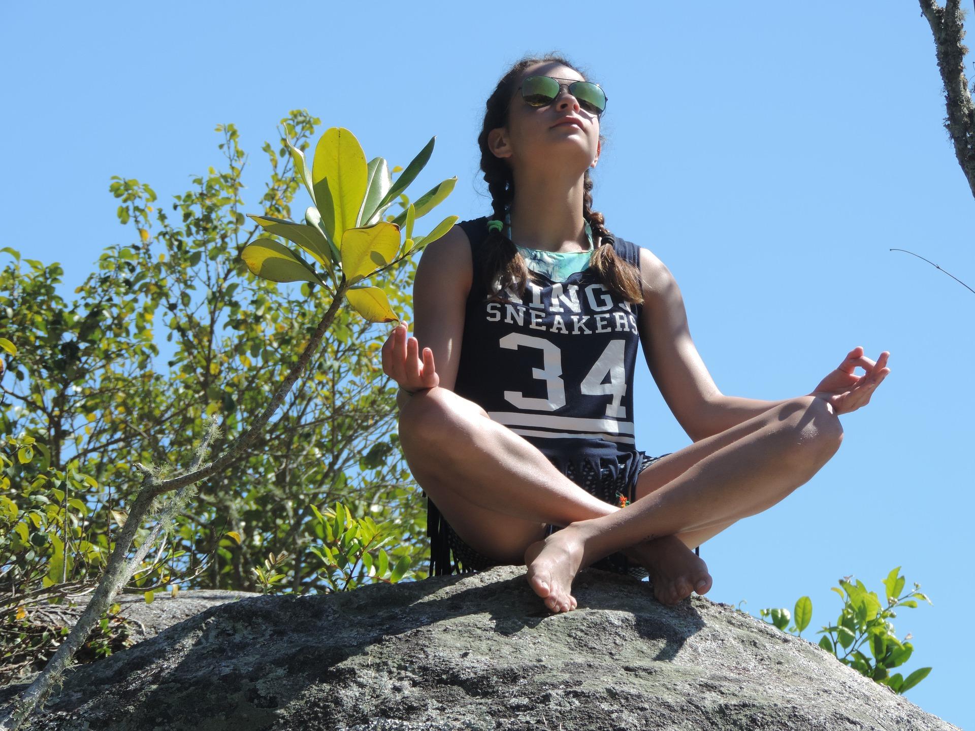 Foto de una mujer haciendo yoga sobre una roca