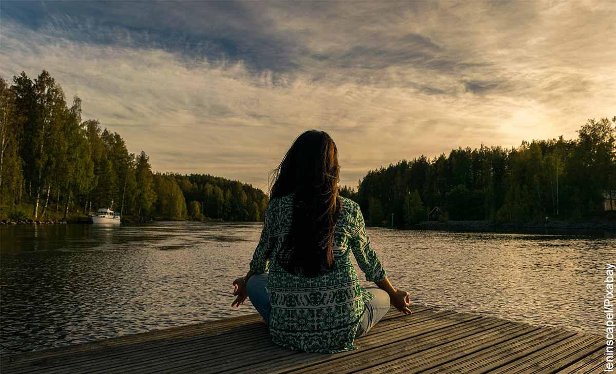 Foto de una mujer sentada en un muelle frente a un lago que muestra para qué sirve la meditación