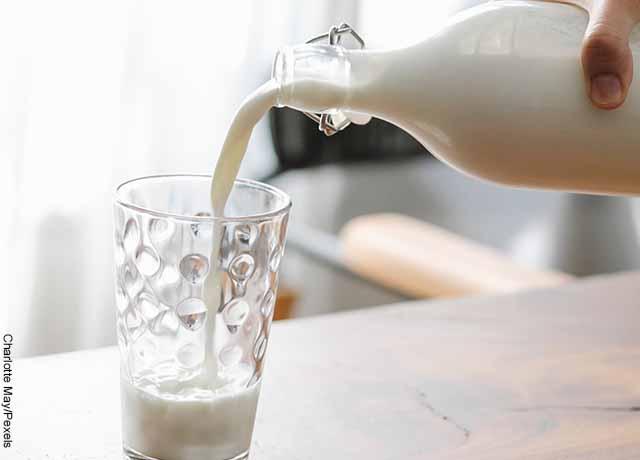 Foto de una persona sirviendo leche en un vaso