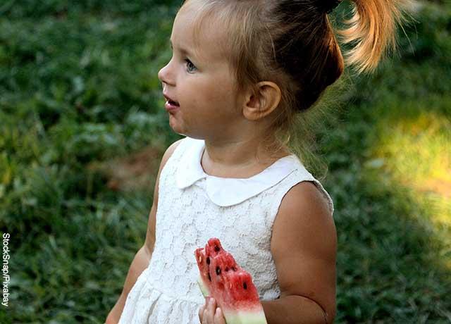 Foto de una niña comiendo patilla