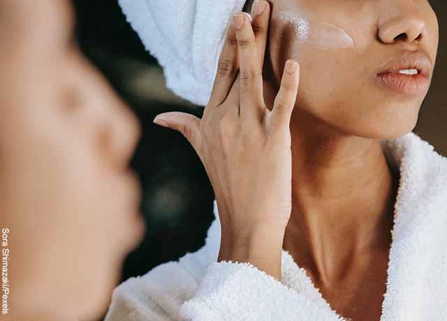 Foto de una mujer aplicando una crema en sus pómulos