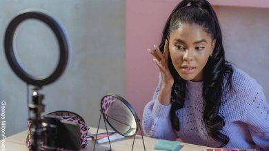 Foto de una mujer aplicando una crema en su rostro en un espejo que revela para qué sirve la vaselina en la cara