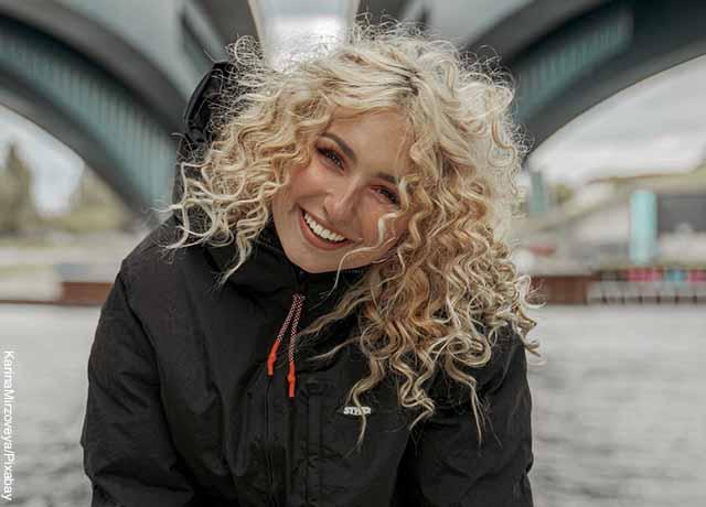 Foto de una mujer sonriente luciendo su cabello rizado rubio