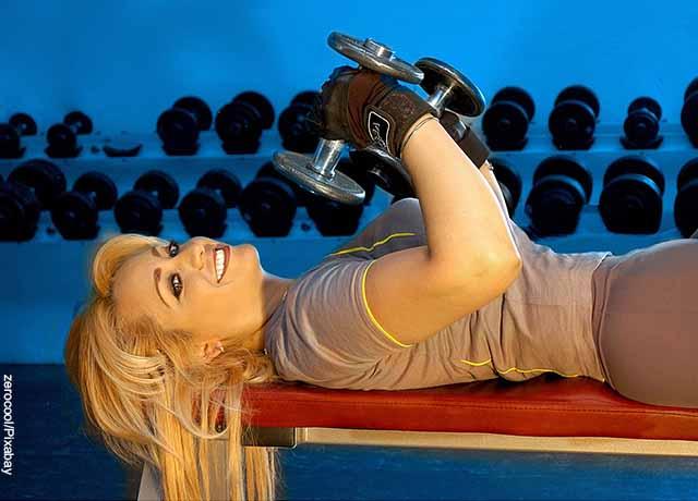 Foto de una mujer acostada levantando pesas