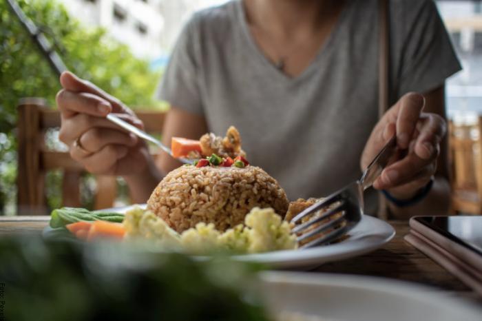 Foto de mujer comiendo arroz