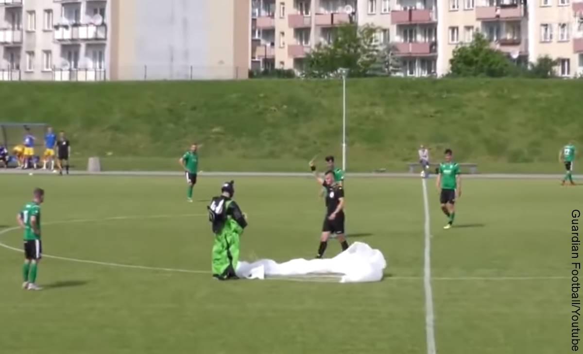 Paracaidista aterriza en cancha de fútbol, ¡y le sacan tarjeta amarilla!