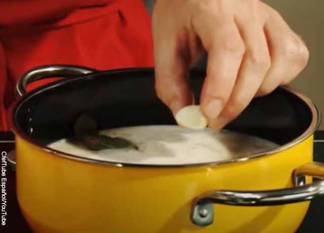 Foto de una persona echando un ajo a una olla
