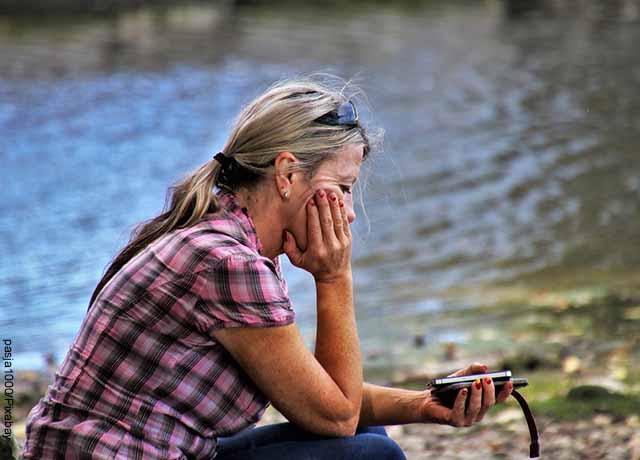 Foto de una mujer sentada mirando su celular al lado de un lago que revela qué hacer cuando estás triste
