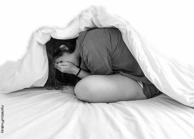 Foto de una mujer metida debajo de las cobijas tomando su rostro