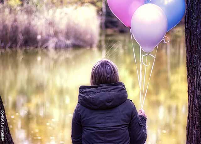 Foto de una mujer sosteniendo unos globos sola