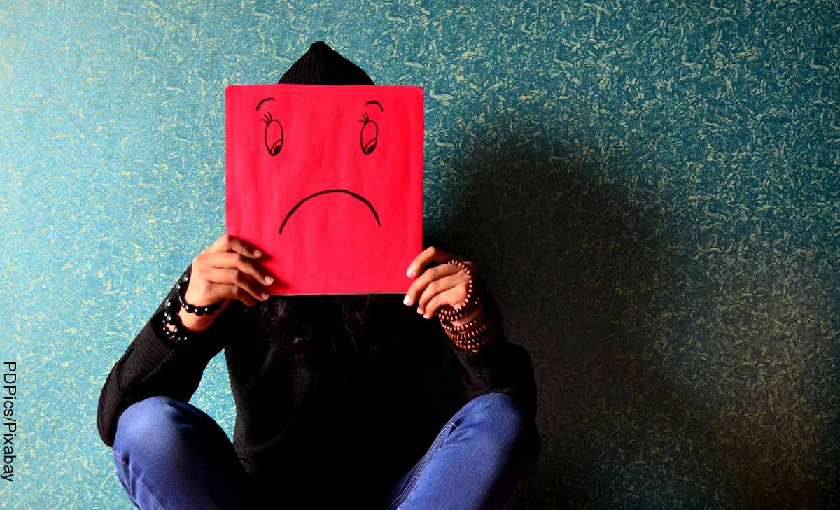 Foto de una persona con una cara triste dibujada en papel que muestra qué hacer cuando estás triste