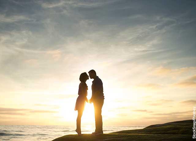Foto de una pareja besándose frente al mar