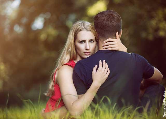 Foto de una mujer abrazando a un hombre mientras mira a la cámara que muestra qué significa soñar con tu crush