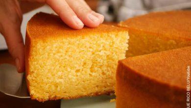Foto de una tajada de ponqué sostenida por una mano que muestra la receta de torta de vainilla