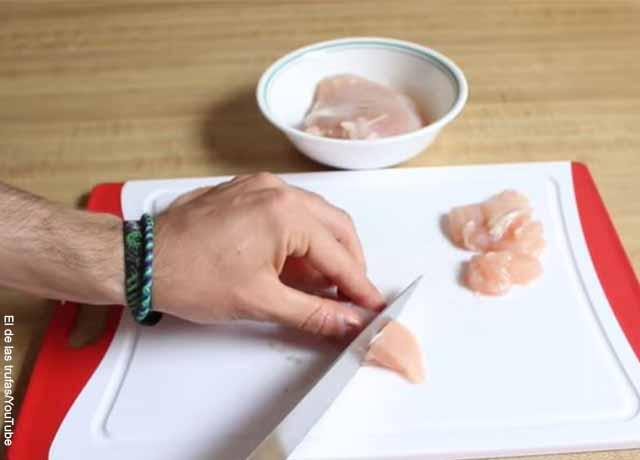 Foto de una persona cortando pollo
