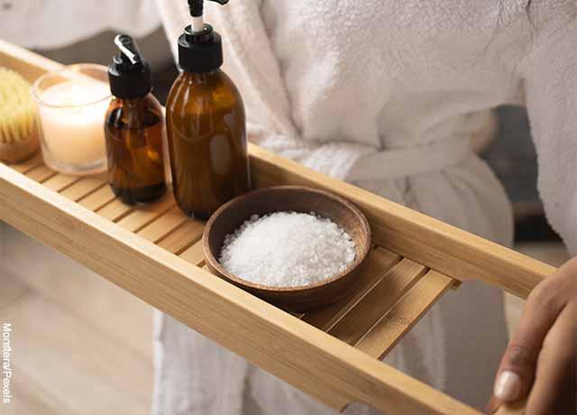 Foto de una mujer sosteniendo productos de limpieza que revela la sal de epsom para qué sirve